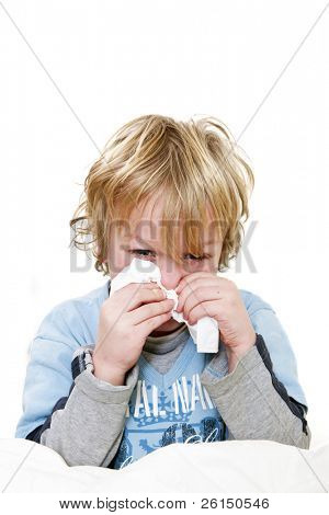 Young boy sitting straight up in his bed, sneezing, with a handkerchief in his hands, and a red head and a tear in his eye from the effort and fever