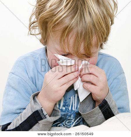 Young boy sneezing in a handkerchief, square close up
