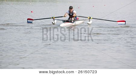Disabled oarsman during the start of a stroke in a skiff