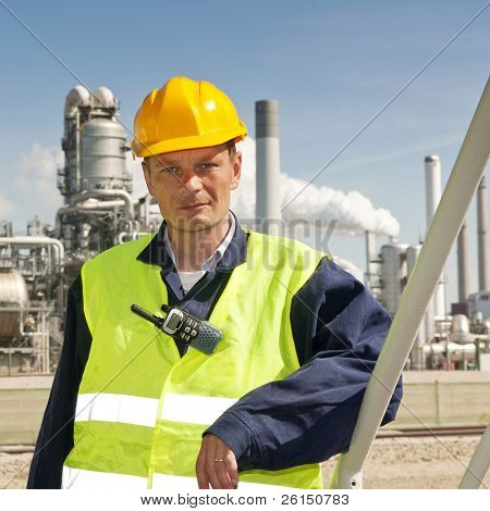 Engineer poses casually in front of a refinery, wearing a safety vest and hard hat