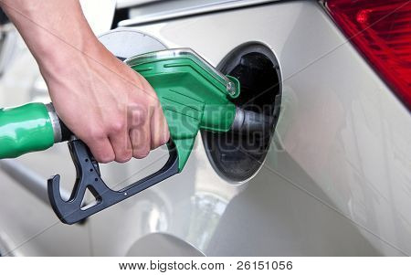 Hand, refuelling a passenger car, holding a green fuel pump