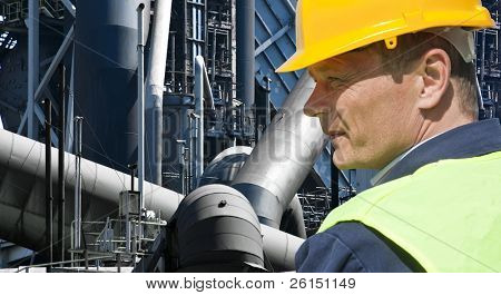 Stern looking worker in front of an imposing factory of a heavy industry facility