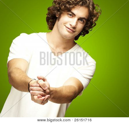 portrait of young man gesturing contract against a green background
