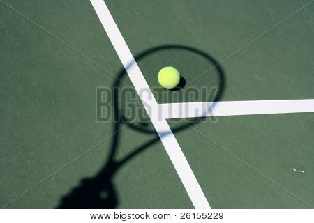 Tennis ball on a court with a racquet shadow