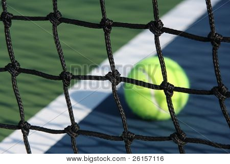 Tennis net with ball and court line in the background