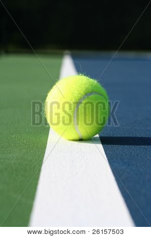 Tennis ball on the line of a multicolored court