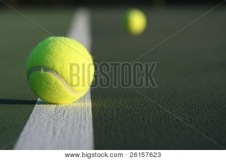 Tennis ball with one faded in the background