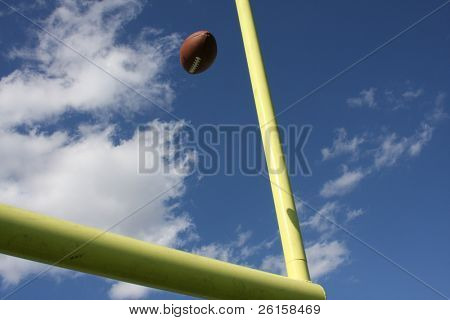 American football kicked through the goal