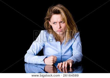 very angry and frustrated young female, hits desk with her fist and scratch it with her nails, studio shoot isolated on black background