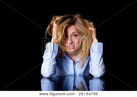 depression, stress, headache concept, attractive woman in blue shirt holds her head, face expression, studio shoot isolated on black background