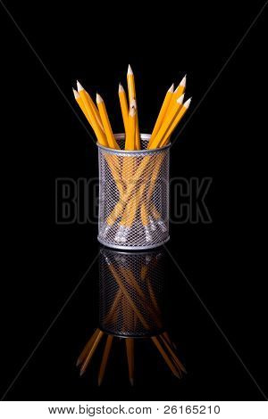 sharp yellow pencils in metal cup, studio shoot isolated on black with reflection