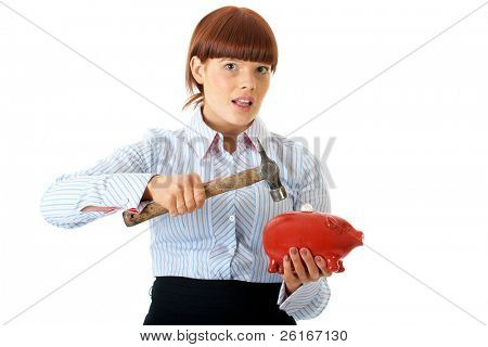 young redhead female trying to break into red piggy bank, spending savings concept, isolated on white
