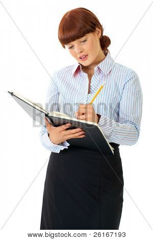 redhead female makes some notes in big black notepad, isolated on white