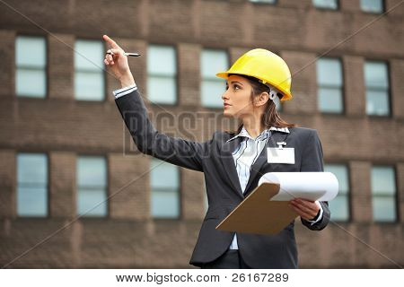 attractive female architect in yellow hard hat point to building, grey suit and shirt