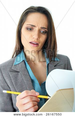young attractive but shocked businesswoman makes some notes or calculation with pencil and paper on wooden board, isolated on white