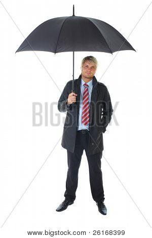 blonde businessman in blue shirt and dark coat holds black open umbrella over his head, isolated on white