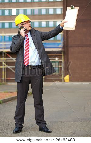 young architect, inspector talk over his mobile phone, outdoor shoot with blurred office building as background