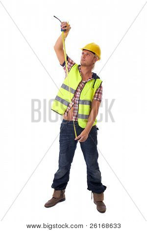 young builder in vest and yellow hardhat measure something, isolated on white background