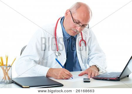 mature doctor in blue shirt and coat sits at his desk, make some notes, isolated on white background
