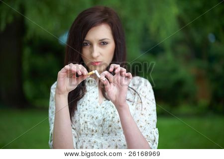 attractive female breaks cigarette, refuse to smoke