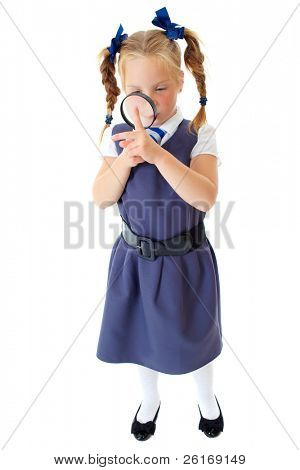 Blonde happy curious schoolgirl in blue dress and matching tie holds magnifying glass, isolated on white