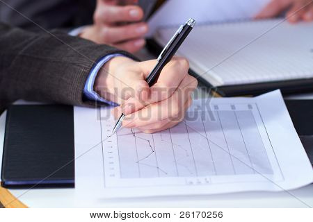 female hand holds pen over graph printed on A4 size document