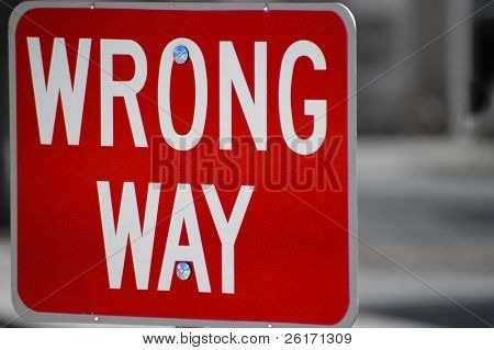Red street sign stating wrong way direction