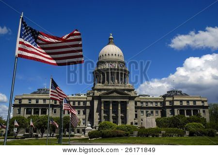 State capitol building with flags and sky
