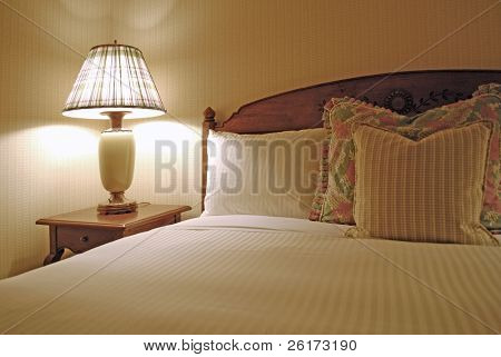 Group of several pillows on a bed with headboard
