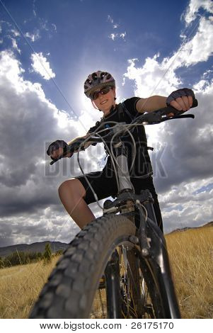 Joven mujer Riding Mountain Bike en el desierto