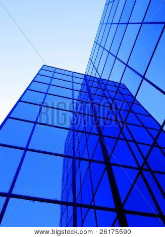 Office building details reflecting, blue sky in geometric windows