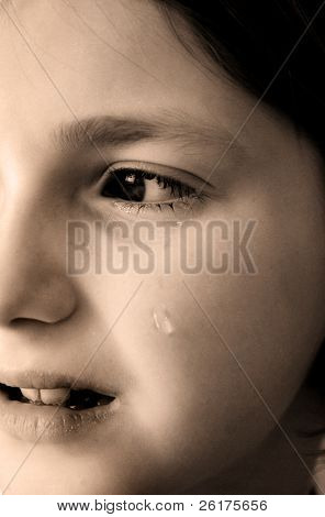 Young girl crying with tear rolling down cheek of face