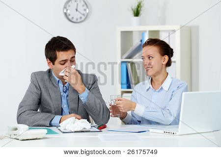 Image of businessman sneezing while his partner giving him tablets and water in office