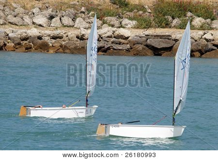 Two optimist class yachts sailing with their young sailors taking it easy