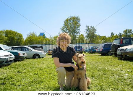 happy smiling woman in her about sixty with her cute Airdale sitting between row of cars on green grass