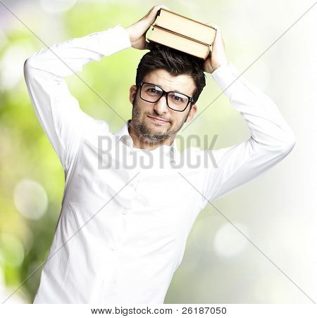 portrait of young student holding books against a nature background