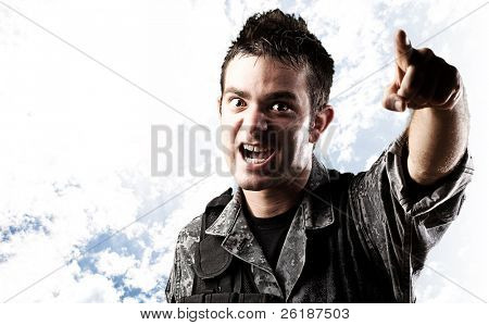portrait of young soldier pointing with finger against a cloudy sky background