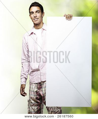 portrait of young man holding banner against a nature background