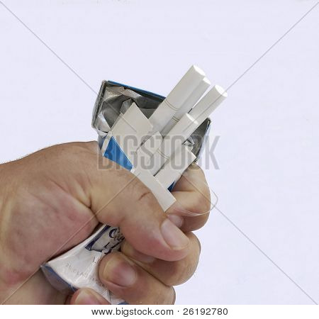 Crushing a packet of cigarettes, symbolising the struggle to beat nicotine addiction.