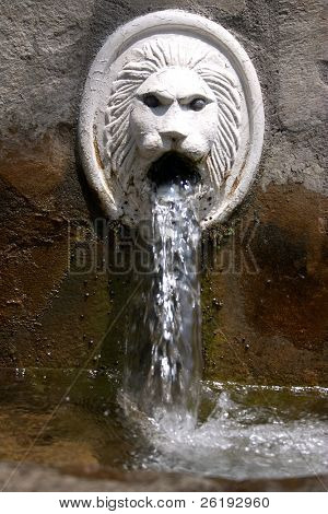 Natural spring water in the mountain village of Spili, Crete, gushes from a lion's mouths in the village square.