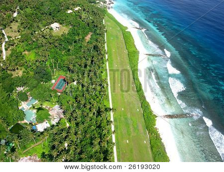 New version: A grass airfield on a Seychelles island, seen from the air, used for helicopters and light aircraft.