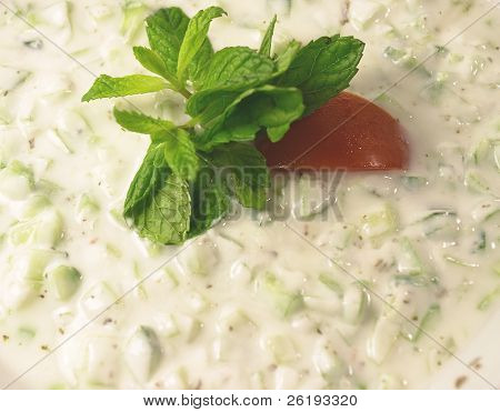 Close-up on a cucumber raita dip (cucumber in yoghourt) garnished with mint and tomato.