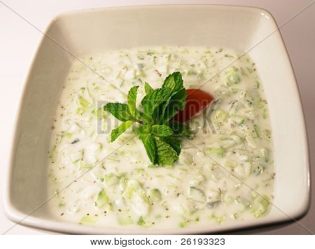 Cucumber raita dip (cucumber in yoghourt) garnished with mint and tomato.