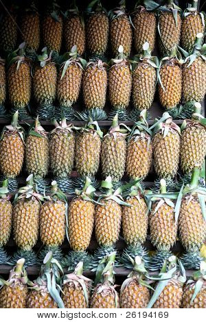 Racks full of pineapples for sale by the roadside in Sri Lanka