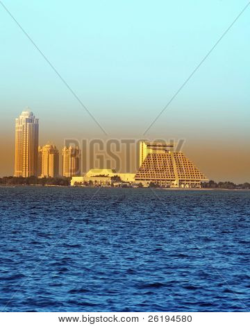 The Doha Sheraton Hotel pyramid and the Four Seasons Hotel towers with the Conference Centre between them, viewed from the Cornice in Doha, Qatar.