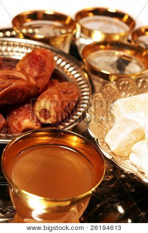 A cup of traditional green coffee (ghawa) with Turkish delight (raha haloum) and dates on a silver tray. Traditional Arab Ramadan fast-breaking treats.