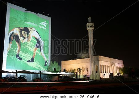 A huge poster advertising the Doha Asian Games hung on a building beside the Abu Bakr Al Siddiqi Mosque in central Doha, Qatar, two months before the December 2006 games