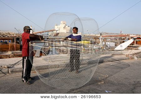 Asian fishermen preparing their fish traps at the Dhow Harbour in Doha, Qatar, April 2008. The new Islamic Art Museum that overlooks Doha Bay is behind them.