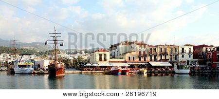 A panoramic view of the Venetian Harbour at Rethymnon, Crete, with the resort city and mountains in the background