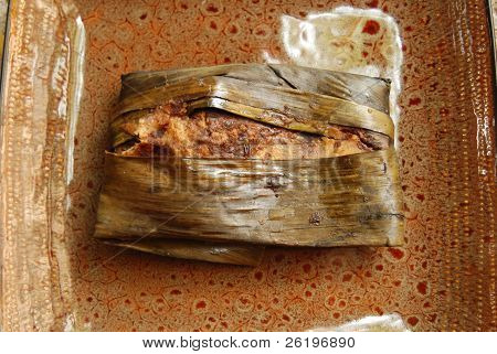 A chicken tamale steamed in a banana leaf with mole sauce